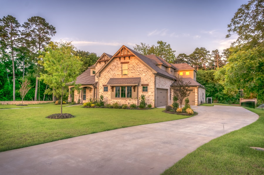 brick house with winding driveway and summer lawn